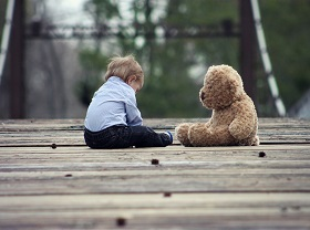 Small boy sitting next to a teddy bear