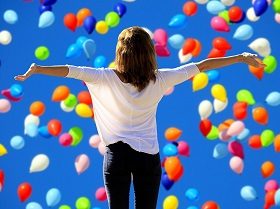 A woman basking in sunlight with a lot of balloons being release in the background
