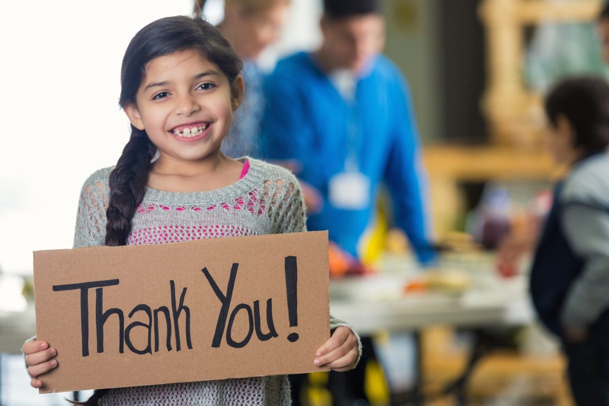 Girl holding a 'Thank You!' sign